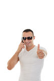 Hombre con las gafas de sol en la camiseta blanca que contesta al teléfono elegante y a s Imagenes de archivo