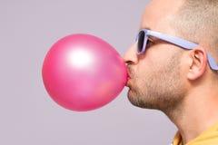 Hombre con las gafas de sol púrpuras que soplan el chicle rosado Fotografía de archivo libre de regalías