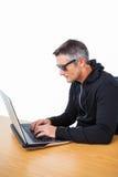 Hombre con las gafas de sol que mecanografía en el ordenador portátil Foto de archivo