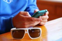 Hombre con las gafas de sol que se sientan en un restaurante y que juegan en un sma Foto de archivo