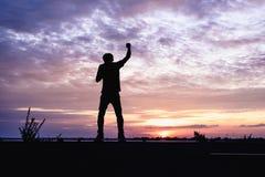 Hombre con las manos aumentadas en la puesta del sol Fotos de archivo