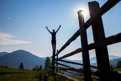 Hombre con las manos para arriba encima de las montañas imagen de archivo