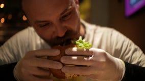 Hombre con las mordeduras de una barba una hamburguesa cheeseburger almacen de video