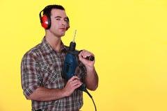 Hombre con las orejeras y el taladro Fotos de archivo libres de regalías