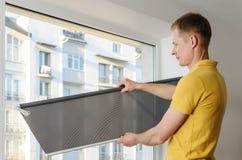 Hombre con las persianas de ventana fotos de archivo libres de regalías