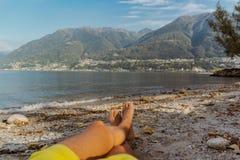 Hombre con las piernas cruzadas que se relajan en a orillas del lago en maggiore de Locarno, lago fotografía de archivo libre de regalías