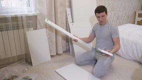 Hombre con las piezas de muebles metrajes