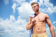 Hombre con las tetas al aire al aire libre con la paja en boca y la camisa en hombro Imágenes de archivo libres de regalías