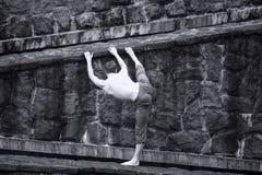 Hombre con las tetas al aire blanco que estira en la pared pedregosa Fotografía de archivo