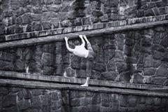 Hombre con las tetas al aire blanco que estira en la pared pedregosa Foto de archivo libre de regalías