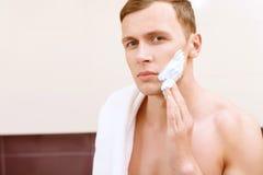 Hombre con las tetas al aire que aplica el medio de afeitar en cara Fotografía de archivo