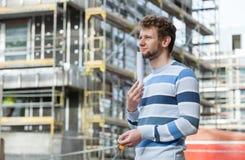 Hombre con llaves en frente de la construcción de nueva viviendas Fotografía de archivo