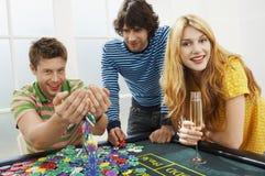 Hombre con los amigos que juegan con Chips At Roulette Table imagen de archivo libre de regalías