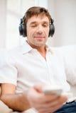 Hombre con los auriculares que escucha la música foto de archivo