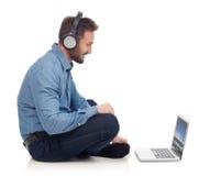 Hombre con los auriculares y la computadora portátil Fotografía de archivo