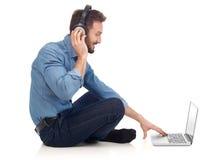 Hombre con los auriculares y la computadora portátil Foto de archivo libre de regalías
