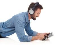 Hombre con los auriculares y la tableta Imágenes de archivo libres de regalías