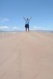 Hombre con los brazos extendidos en la cima de la montaña Imagenes de archivo