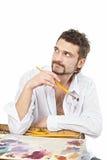 Hombre con los cepillos y la sentada de la paleta Aislado sobre blanco foto de archivo libre de regalías