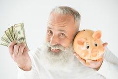 Hombre con los dólares y la hucha Fotografía de archivo libre de regalías