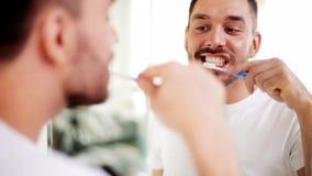 Hombre con los dientes de la limpieza del cepillo de dientes en el cuarto de baño metrajes