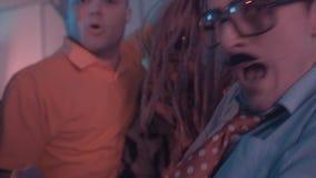 Hombre con los dreadlocks y el abrigo de pieles del leopardo que baila para arriba en el sitio ahumado del partido almacen de metraje de vídeo