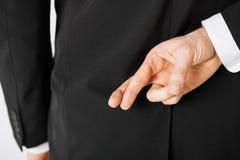 Hombre con los fingeres cruzados Fotografía de archivo libre de regalías