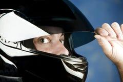 Hombre con los ojos abiertos en un casco de la motocicleta Fotos de archivo libres de regalías
