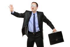 Hombre con los ojos vendados perdido con un billete de banco en sus ojos Imagen de archivo