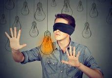 Hombre con los ojos vendados que camina a través de las bombillas que buscan para la idea Foto de archivo libre de regalías