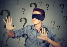 Hombre con los ojos vendados que camina a través de muchos signos de interrogación fotos de archivo libres de regalías