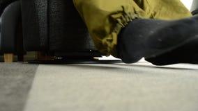 Hombre con los pantalones verdes y los calcetines negros que se sientan en una silla negra almacen de video