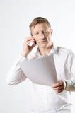 Hombre con los papeles en el teléfono Imagen de archivo libre de regalías