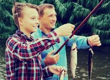 Hombre con los pescados de la captura de la demostración del muchacho del adolescente Imagen de archivo libre de regalías