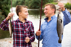 Hombre con los pescados de la captura de la demostración del muchacho del adolescente Fotos de archivo