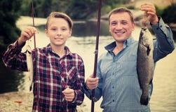 Hombre con los pescados de la captura de la demostración del muchacho del adolescente Foto de archivo