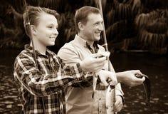 Hombre con los pescados de la captura de la demostración del muchacho del adolescente Fotos de archivo libres de regalías