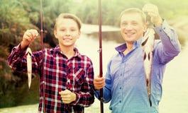 Hombre con los pescados de la captura de la demostración del muchacho del adolescente Fotografía de archivo