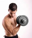 Hombre con los pesos de las pesas de gimnasia que hacen ejercicio de los bieps Imagenes de archivo