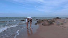 Hombre con los pies desnudos que camina cerca de la playa metrajes