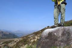 Hombre con los polos que caminan que se colocan en la roca en la cuesta de la montaña Imágenes de archivo libres de regalías