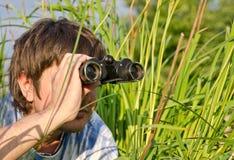 Hombre con los prismáticos en alta hierba Foto de archivo libre de regalías