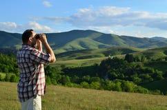 Hombre con los prismáticos el día de verano Imágenes de archivo libres de regalías