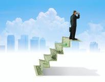 Hombre con los prismáticos en las escaleras del dinero que busca el anuncio financiero del éxito Imagen de archivo libre de regalías