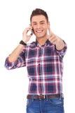 Hombre con los pulgares para arriba en el teléfono Foto de archivo