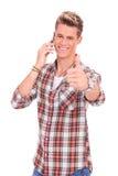 Hombre con los pulgares para arriba mientras que en el teléfono Foto de archivo libre de regalías