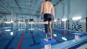 Hombre con los soportes de la pierna artificial cerca de un entrenamiento del rato de la piscina almacen de video