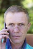 Hombre con los vidrios con el teléfono Fotos de archivo libres de regalías