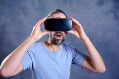 Hombre con los vidrios de la realidad virtual que señala parecer sorprendido Fotografía de archivo