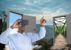 hombre con los vidrios de VR en el bosque con dos puertas a ir el otro lugar fotos de archivo libres de regalías
